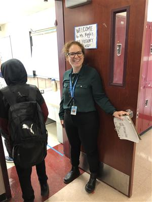 Ms. Rygh standing at her classroom door