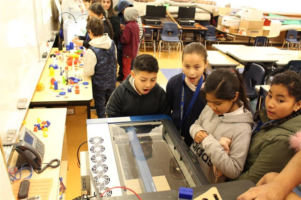 Dover Elementary Student look on as the Mobile Fab Lab creates name tags with a laser cutter