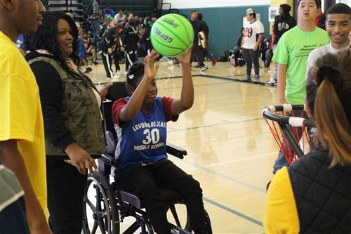 Members of DeJean Middle Schools team assist each other at the 3rd Annual Special Olympics Basketball Tournament.