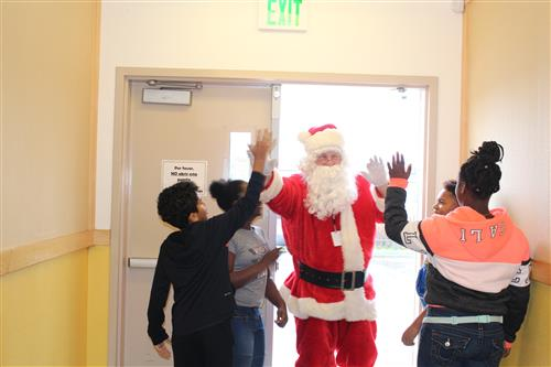 WCCUSD Warehouse Supervisor and District Santa Jim Gant greeting 6th graders at King elementary school.