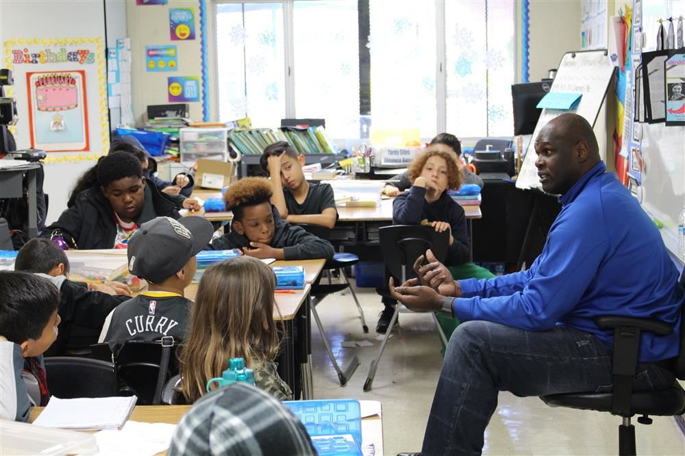 Former Warriors Center Adonal Foyle talks with Wilson Elementary School students.