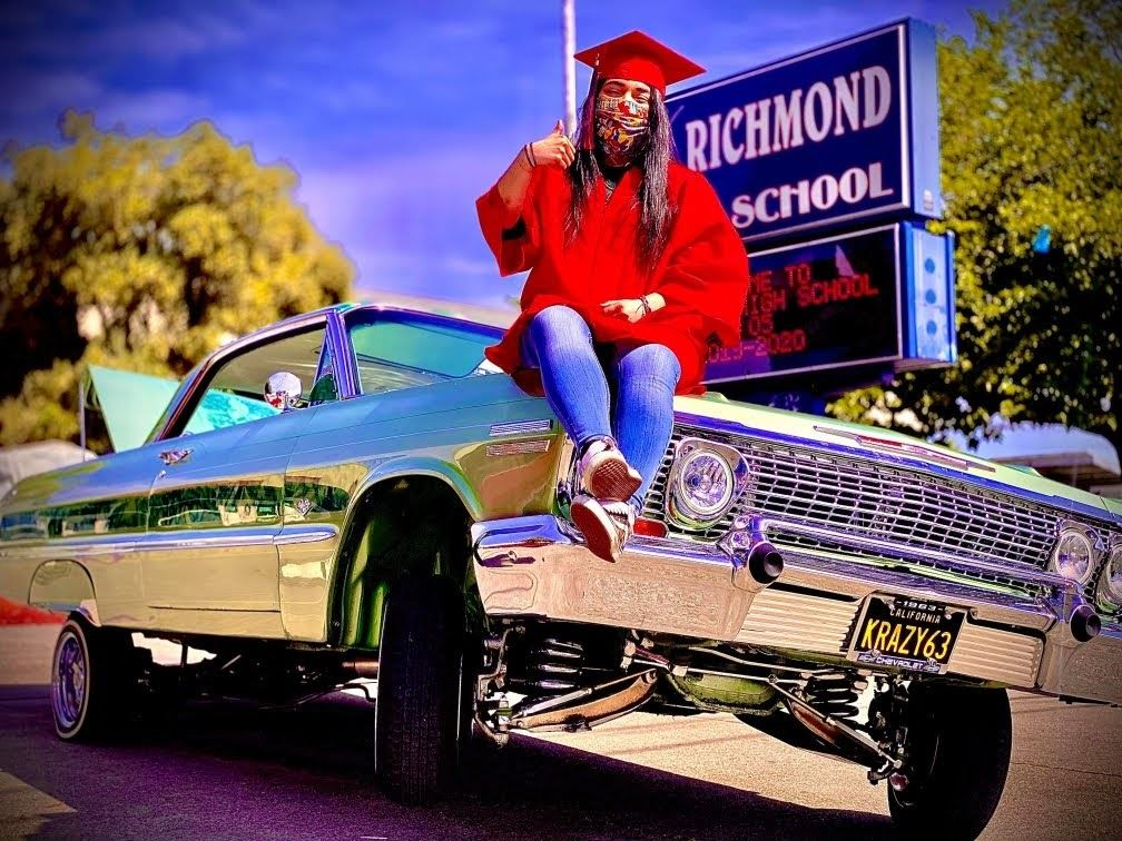 graduate sitting on top of vehicle