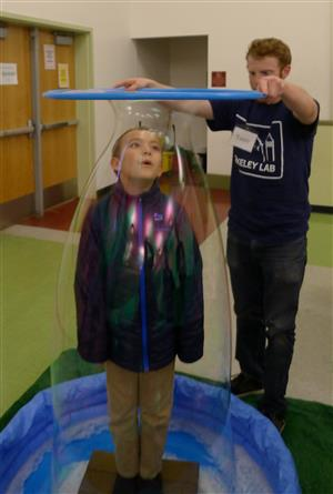 Teacher and student creating human-sized bubbles