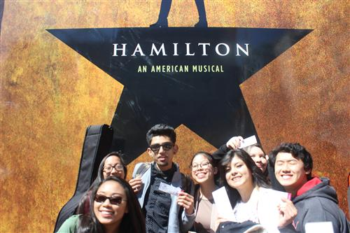 Richmond HS students poses in front of the Hamilton logo
